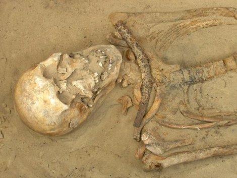 Hombre adulto de 35 a 44 años. Una guadaña lo sujeta a su sepulcro.